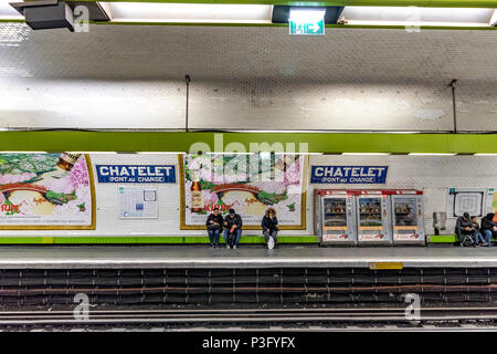 People sitting waiting for a train on Châtelet Pont Au Change station on The Paris Metro ,France - Stock Photo