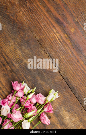 Eustoma, lisianthus flower arranged as a natural image on aged brown wooden background with soft white and pink blossoms and copy space for text - Stock Photo
