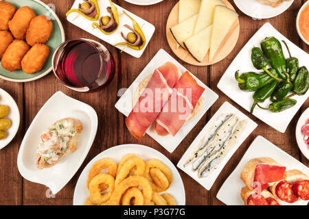 The food of Spain. An overhead photo of various Spanish tapas, shot from above on a dark rustic texture. Jamon, cheese, wine, olives, croquettes, cala - Stock Photo