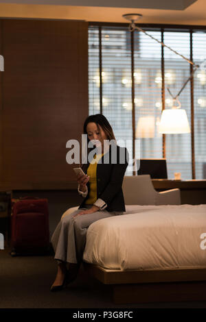 Businesswoman sitting on bed using her mobile phone - Stock Photo