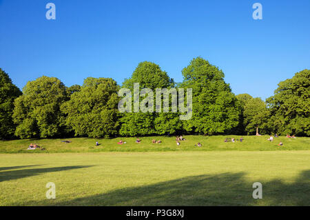 People relaxing in the sun on the grassy banks of Kensington Gardens, Royal Borough of Kensington and Chelsea, London, England, UK - Stock Photo