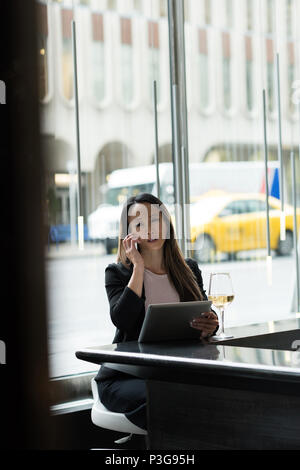 Businesswoman talking on phone while using her tablet - Stock Photo