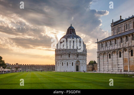 Dramatic sunset over the Piazza dei Miracoli (Piazza del Duomo) with medieval round Romanesque Baptistery of St. John (Pisa Baptistry) and Duomo Pisa  - Stock Photo