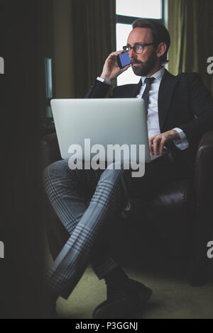 Businessman talking on mobile phone while using laptop - Stock Photo