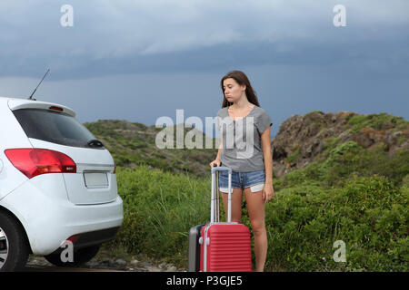 Frustrated car driver waiting for assistance after breakdown with a storm in the background - Stock Photo