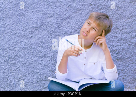 Boy with pencil and open notebook sitting on the ground and thinking, creating or calculating - Stock Photo
