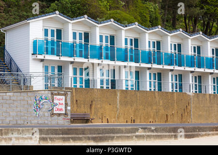 Beach huts with Follow your Dreams mural at Branksome Chine, Poole, Dorset, England UK in June - Stock Photo