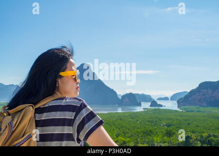 Happy young traveler woman backpacker looking at mountain with sea and enjoying a beautiful of nature at ,Freedom wanderlust,Khao Samed Nang Chee View - Stock Photo