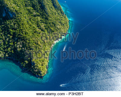 Aerial drone view down onto boats over a tropical coral reef surrounded by mountains and jungle - Stock Photo