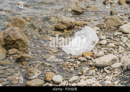 Empty plastic bag dumped in the water. Pollution concept. - Stock Photo
