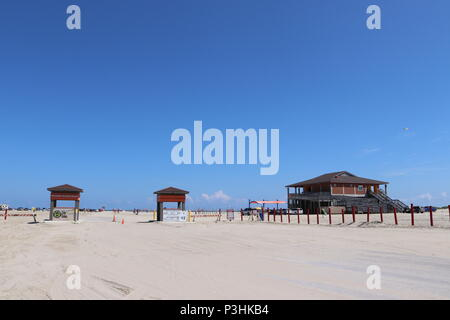 American beach lifestyle. Beach with blue sky on the Gulf Coast, Texas, Galveston Island, USA. Beach entrance for cars, campers to drive on the beach. - Stock Photo