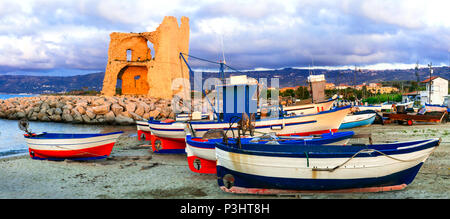 Old tower over sunset in Briatico,view with traditional fishing boats,Calabria,Italy. - Stock Photo