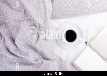 The cup of coffee and paper notebook with pencil on grey bed. Top view, morning mood concept. - Stock Photo