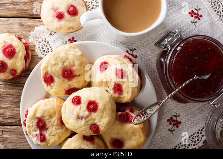 English sconces biscuits with red currants are served with tea and milk close-up on the table. horizontal top view from above - Stock Photo