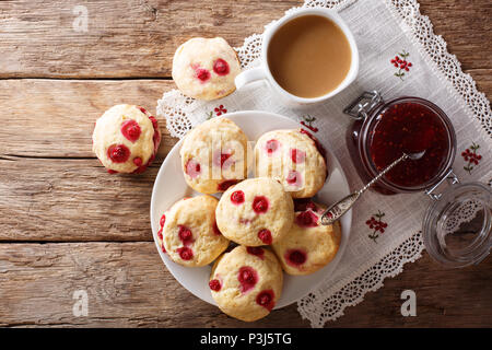English buns sconces with red currants are served with English tea and jam close-up on the table. horizontal top view from above - Stock Photo