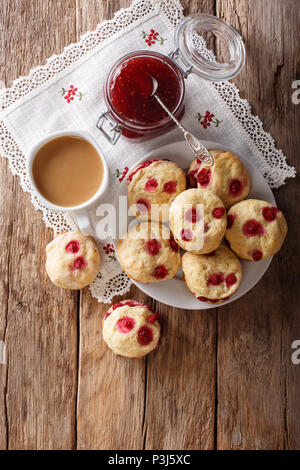 English buns sconces with red currants are served with English tea and jam close-up on the table. Vertical top view from above - Stock Photo