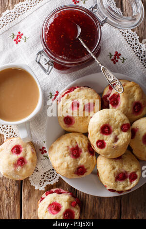 English sconces biscuits with red currants are served with tea and milk close-up on the table. Vertical top view from above - Stock Photo