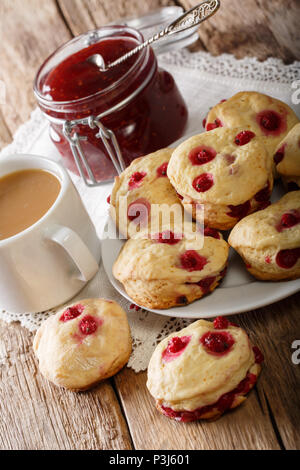 Delicious sconces biscuits with red currants are served with tea with milk and jam close-up on the table. vertical - Stock Photo