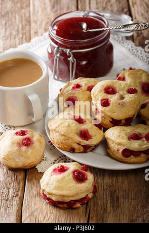 Homemade sconces with red currants are served with English tea with milk and jam close-up on the table. vertical - Stock Photo