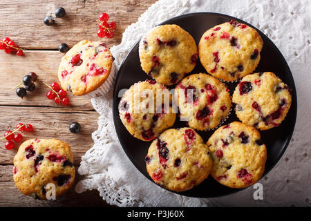 Freshly baked muffins with black and red currant berries close-up on the table. horizontal top view from above - Stock Photo
