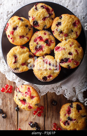 Freshly baked muffins with black and red currant berries close-up on the table. Vertical top view from above - Stock Photo