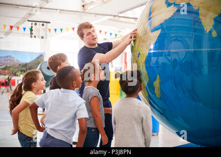 Kids watch presentation with giant globe at a science centre - Stock Photo