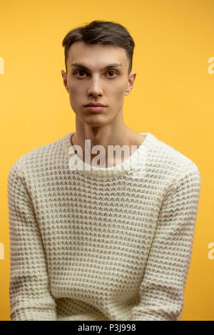 Portrait of a smart serious young man standing against yellow background - Stock Photo