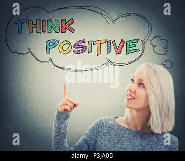 Portrait of smiling woman pointing her finger up to a thought bouble with the text think positive. Colorful motivatinal slogan, having fun, enjoy the  - Stock Photo