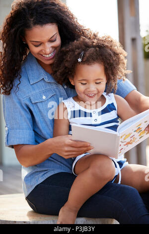 Young black girl reading book sitting on mum's knee outdoors