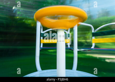 Picture of a merry-go-round (playground equipment) taken in movement. Long exposure to show how it spins and motion. - Stock Photo