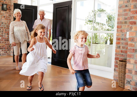 Young brother and sister arriving home with grandparents - Stock Photo
