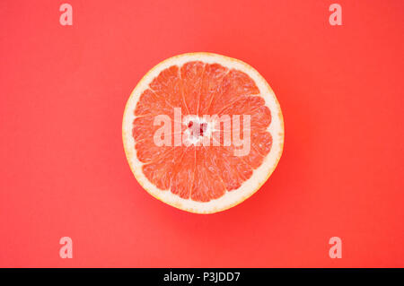 Beautiful juicy cut grapefruit on red background. - Stock Photo