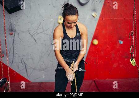 Woman climber tying rope in knot and preparing to climb. Climbing equipment - Stock Photo