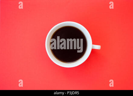 A cup of fresh black coffee on red background with text space. - Stock Photo