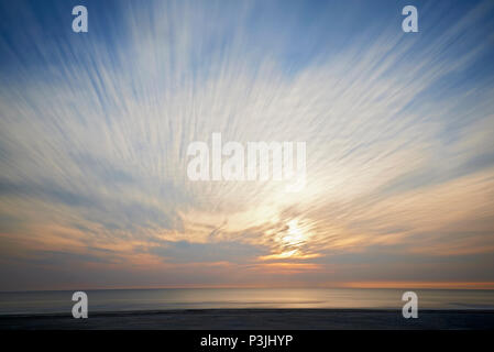 Wide angle shot of an empty beach with calm sea and clouds moving in one direction in a long exposure during sunset - Stock Photo