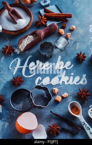 Pastry recipe concept from above with baking tools and ingredients. Food typography with Here be Cookies text on a marble table - Stock Photo