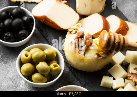 Snacks with wine - various types of cheeses, figs, nuts on a gray background - Stock Photo