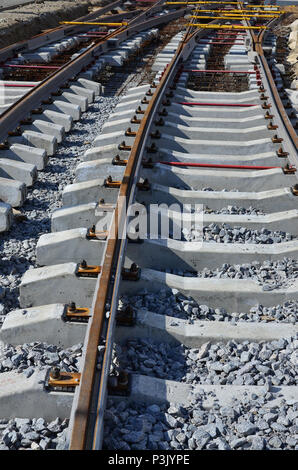 Fragment of tram rails at the stage of their installation and integration into the road. The process of laying a tramway - Stock Photo