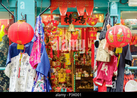 A souvenir shop front decorated with red lanterns, Chinese costumes and ornaments in London Chinatown - Stock Photo