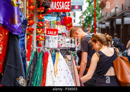 London, UK - July 01, 2018 - Tourists browsing outside a clothing and souvenir shop in Chinatown - Stock Photo