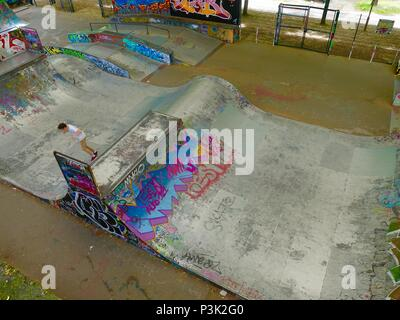 Boy in skatepark decorated with grafitti at Bercy Park, Paris, France - Stock Photo