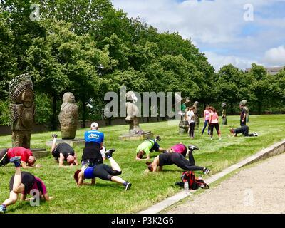 Fitness class works out among statues of the 'Children of the World,' any artist Rachid Khimoune, Bercy Park, Paris, France - Stock Photo