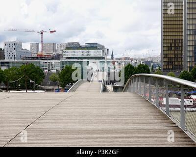 People walking on the Passerelle Simone-de-Beauvoir pedestrian bridge across the Seine River, looking south towards the library, Paris, France. - Stock Photo