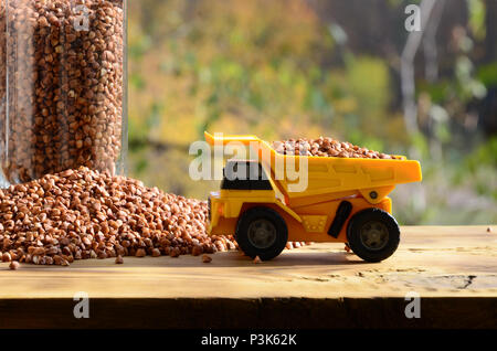 A small yellow toy truck is loaded with brown grains of buckwheat around the buckwheat pile and a glass of croup. A car on a wooden surface against a  - Stock Photo