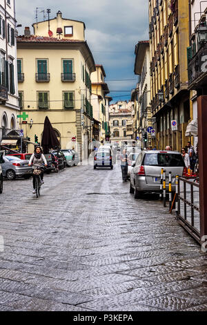Florence, Italy - June 9, 2016:  Pedestrians along a narrow cobblestone road in the city of Florence, Italy. - Stock Photo