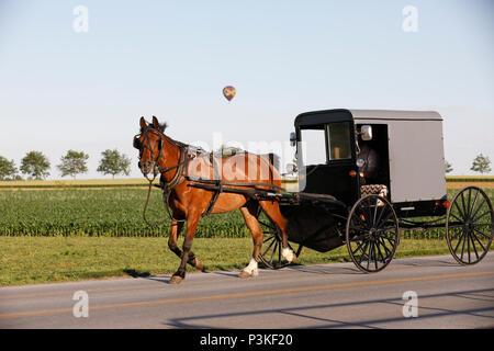 Hot air balloon over Amish buggy, Lancaster County, Pennsylvania, USA - Stock Photo