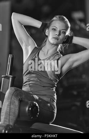 Woman doing strength exercises for abdominal muscles at indoor sport gym. Girl doing yoga stretches after running. Fitness model in dark sport club. B - Stock Photo