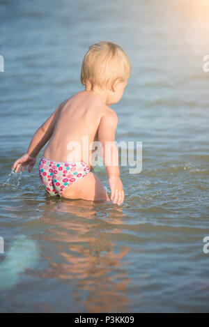Baby playing on the sandy beach and in sea water. Cute little kid with toys on sand tropical beach. Ocean coast. - Stock Photo