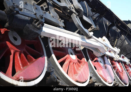 Red wheels of old USSR black steam locomotive. Wheels of an old soviet steam train - Stock Photo