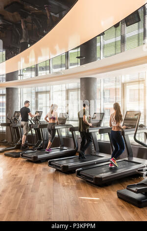 Group of four people running on treadmills in fitness gym - Stock Photo